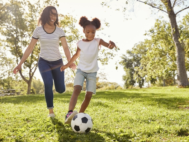 girl playing soccer with her mom